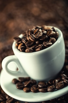 Kaffeebohnen. kaffeetasse voller kaffeebohnen. getöntes bild