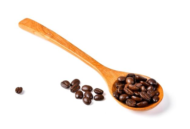 Kaffeebohnen lokalisiert in einem hölzernen löffel auf weißem hintergrund