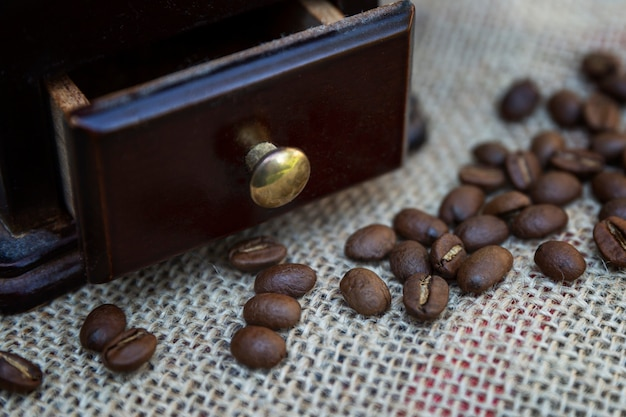 Kaffeebohnen mit einer hölzernen kaffeemühle auf einer leinwand. zubereitung eines aromatischen getränks. nahaufnahme.