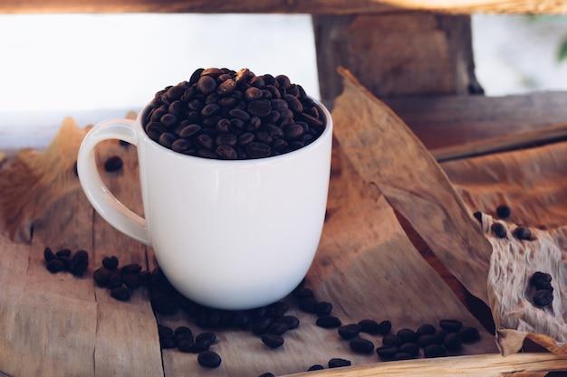 Kaffeebohnen mit einer tasse auf dem tisch