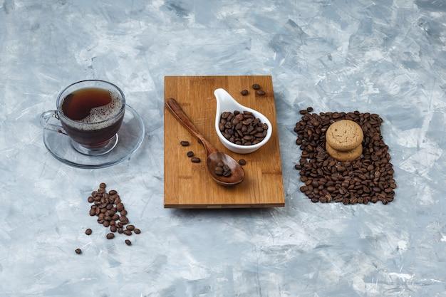 Kaffeebohnen mit hohem blickwinkel, holzlöffel auf schneidebrett mit keksen, tasse kaffee auf hellblauem marmorhintergrund. horizontal