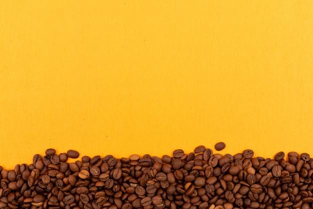 Kaffeebohnen mit kopienraum auf gelber oberfläche