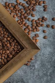 Kaffeebohnen mit leerem rahmen auf einer marmoroberfläche.