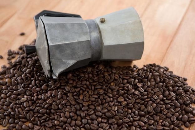 Kaffeebohnen mit metallischer kaffeemaschine