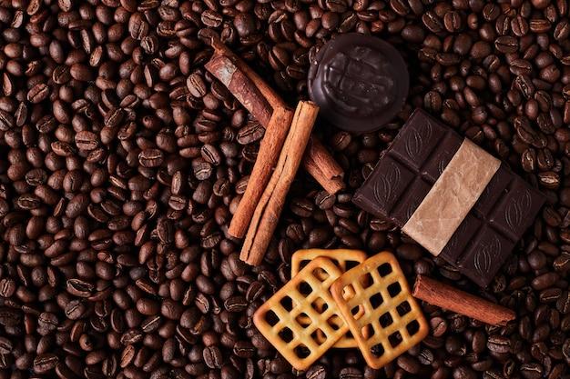 Kaffeebohnen mit schokoladenstücken und keksen.