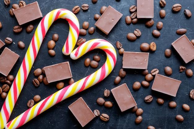 Kaffeebohnen mit schokoladenstücken und stocksüßigkeiten in der herzform auf flacher ansicht des schwarzen hintergrundes