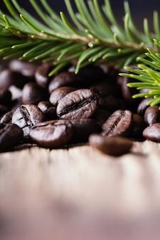 Kaffeebohnen mit tannenbaumniederlassung auf holzoberfläche.