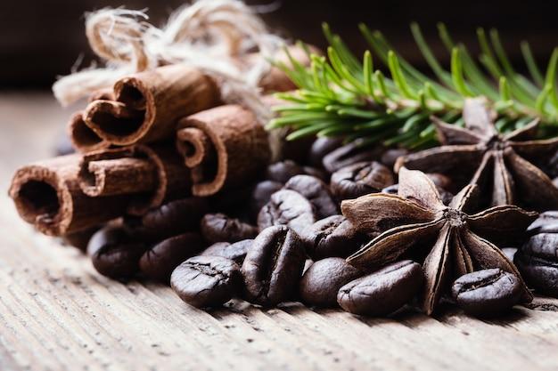 Kaffeebohnen mit zimtstangen, anis, tannenbaumniederlassung auf holzoberfläche.