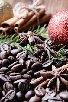 Kaffeebohnen mit zimtstangen, anis, tannenzweig und weihnachtskugeln.