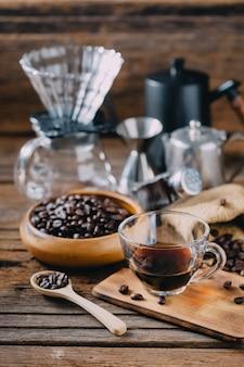 Kaffeebohnen mit zusätzlichem filterkaffee auf holztisch