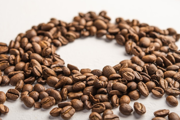 Kaffeebohnen-nahaufnahme verstreut auf einer hellen oberfläche, die für textselektiven fokus zentriert wird