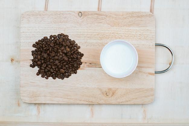 Kaffeebohnen stapelten sich neben den kaffeetassen auf dem brett.