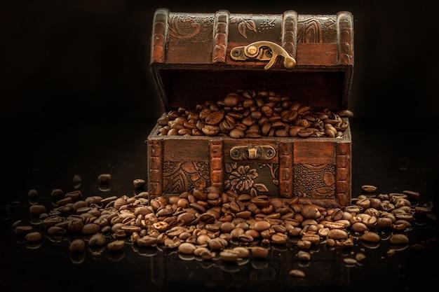 Kaffeebohnen und alte schatztruhe auf schwarzem hintergrund - das schwarze gold