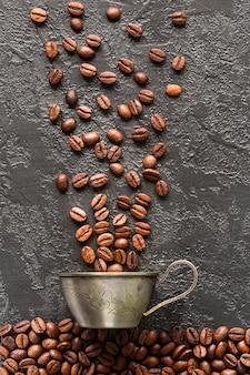 Kaffeebohnen und becher auf grauem konkretem hintergrund