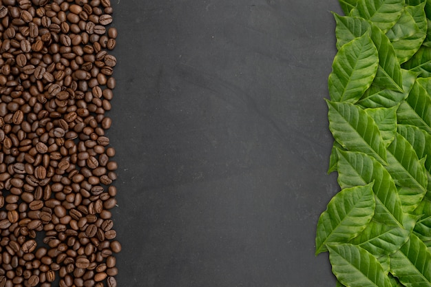 Kaffeebohnen und blätter auf schwarzem holztisch