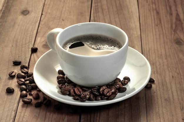 Kaffeebohnen und ein weißer tasse kaffee auf hölzernem hintergrund