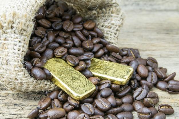 Kaffeebohnen und goldbarren in der sackleinentasche auf hölzernem hintergrund