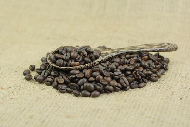 Kaffeebohnen und holzlöffel auf jutefaserbeutelhintergrund