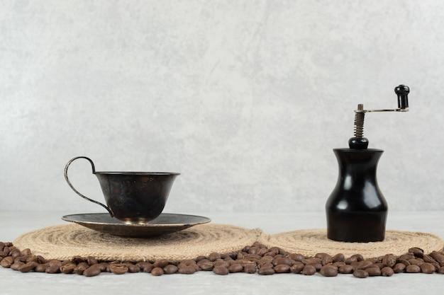 Kaffeebohnen und kaffeemühle auf marmoroberfläche