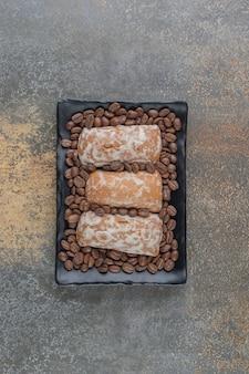 Kaffeebohnen und kekse auf einer schwarzen platte
