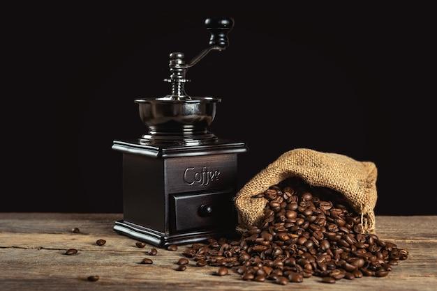 Kaffeebohnen und manuelle retro-kaffeemühle auf holztisch