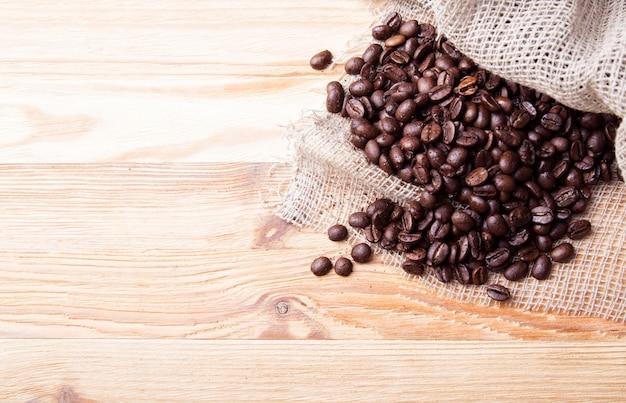 Kaffeebohnen und rostiger beutelhintergrund. draufsicht