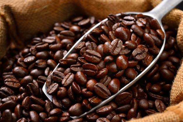 Kaffeebohnen und schaufel im leinensack