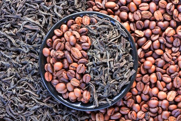 Kaffeebohnen und schwarze teeblätter in einer runden untertasse