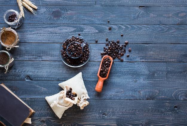 Kaffeebohnen und tasse kaffee mit anderen komponenten auf unterschiedlichem hölzernem hintergrund.