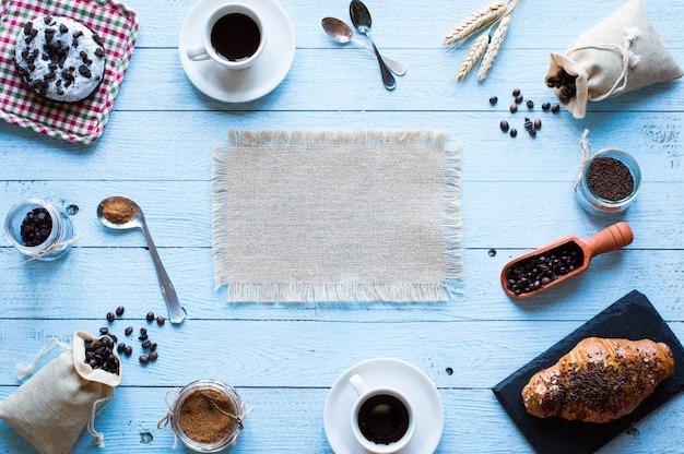 Kaffeebohnen und tasse kaffee mit anderen komponenten auf unterschiedlicher holzoberfläche.