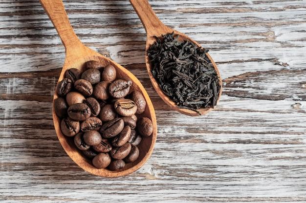 Kaffeebohnen und tee in holzlöffeln