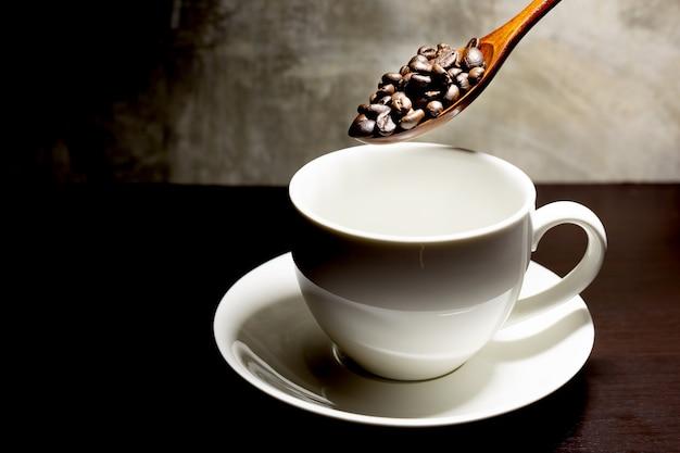 Kaffeebohnen und weiße tassen auf dem tisch