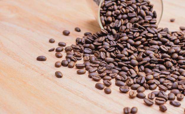 Kaffeebohnen verschüttet aus im glas auf holztisch