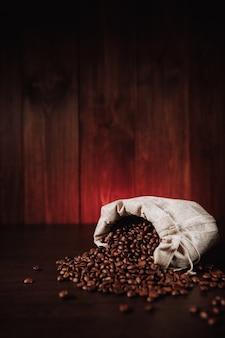 Kaffeebohnen verstreut von der tasche auf holzhintergrund. vertikales bild.