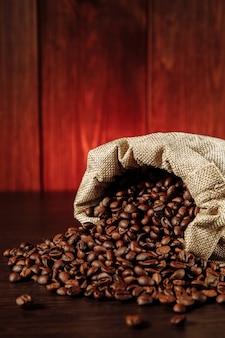 Kaffeebohnen verstreut von der tasche auf holztischnahaufnahme. vertikales bild.