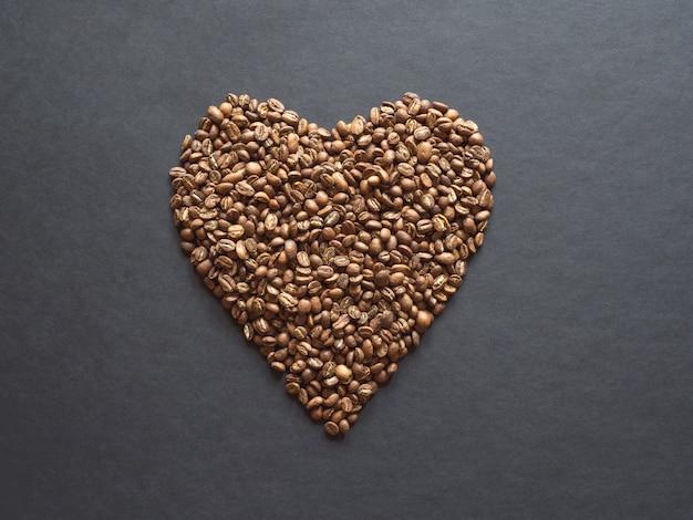 Kaffeebohnen werden in form eines herzens auf einem schwarzen tisch ausgelegt.