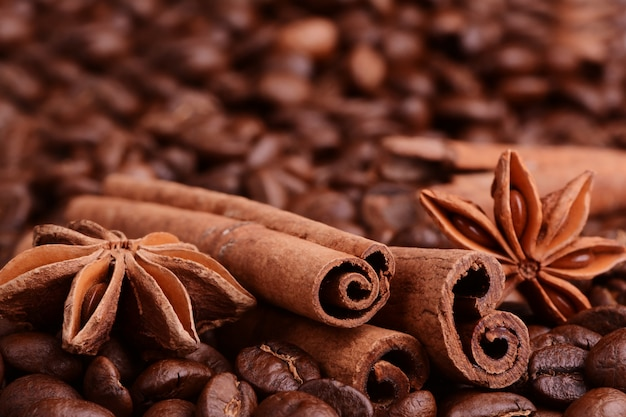 Kaffeebohnen, zimt, sternanis auf dem rausschmiß des hintergrundes.