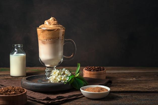 Kaffeedessert mit milch und eis auf einer braunen wand dalgona-kaffee.