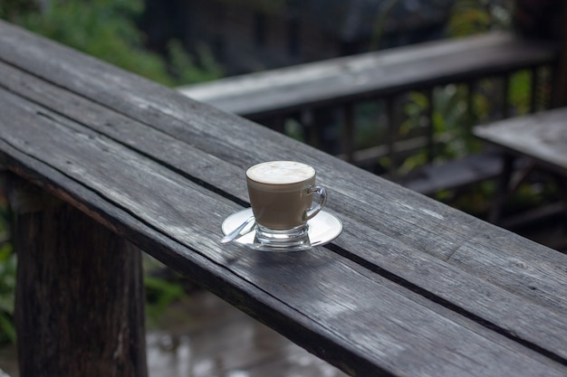 Kaffeeespresso auf hölzernem tabellennaturhintergrund im garten
