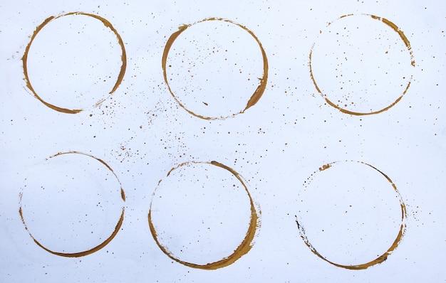 Kaffeeflecken fallen auf weißen hintergrund