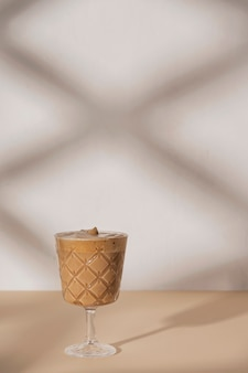 Kaffeegetränk in einem stielglas auf einem beige und weißen neutralen hintergrund mit schatten von der sommersonne. hintergrund mit kopierraum