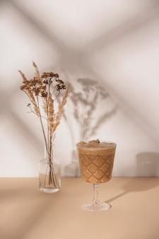 Kaffeegetränk in einem stielglas mit einem strauß getrockneter blumen auf einem neutralen beige-weißen hintergrund mit schatten von der sommersonne. hintergrund mit kopierraum