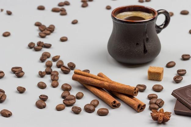 Kaffeegetränk in schwarzer tasse. zimtstangen, schokoladenstücke und kaffeekörner auf dem tisch. grauer hintergrund. ansicht von oben