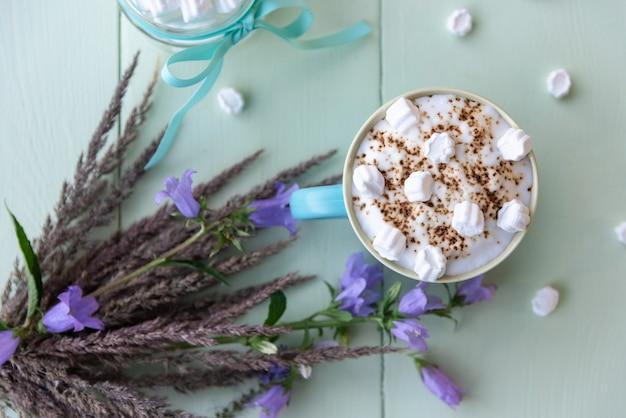 Kaffeegetränk mit geschlagenem schaum und marshmallows auf hellem azurblau.