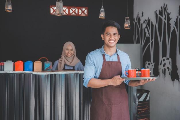 Kaffeehausbesitzer, der tablett hält