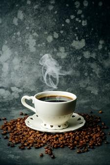 Kaffeehintergrund. kaffeebohnen und tasse auf dunklem hintergrund. kaffeebanner für menü, design und dekoration