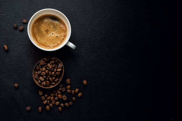 Kaffeehintergrund mit kaffeebohnen, kaffee und löffel auf dunklem hintergrund. sicht von oben. kaffeekonzept.