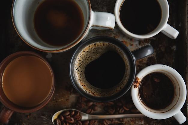 Kaffeehintergrund mit kaffeebohnen, kaffee und löffel auf dunklem hintergrund. von oben betrachten. kaffee-konzept.