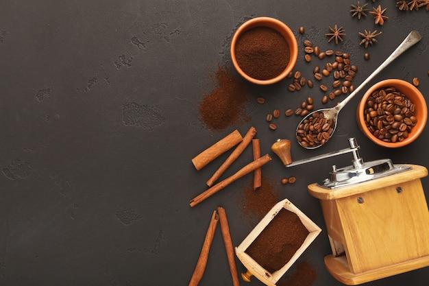Kaffeehintergrund mit vintage-schleifer, bohnen und gewürzen auf schwarzem schiefer, draufsicht, kopienraum. horizontales design zum abwenden von cafés oder coffeeshops