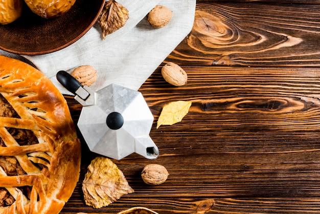 Kaffeekanne in der nähe von blättern und snacks